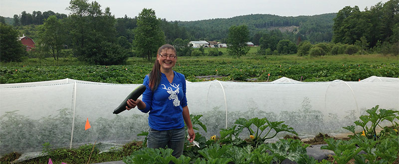Vermont Gleaning Collective member at Greenhouse holding cucumber